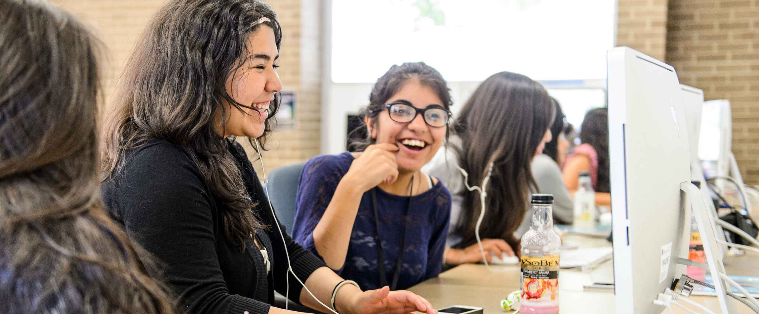 Girls laughing in front of computer