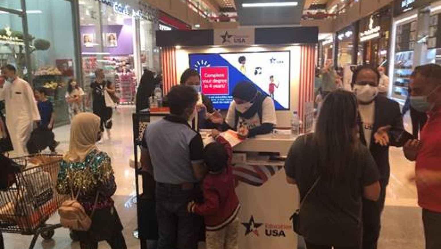 EducationUSA staff speak with visitors at its Kiosk at Doha Festival City Mall